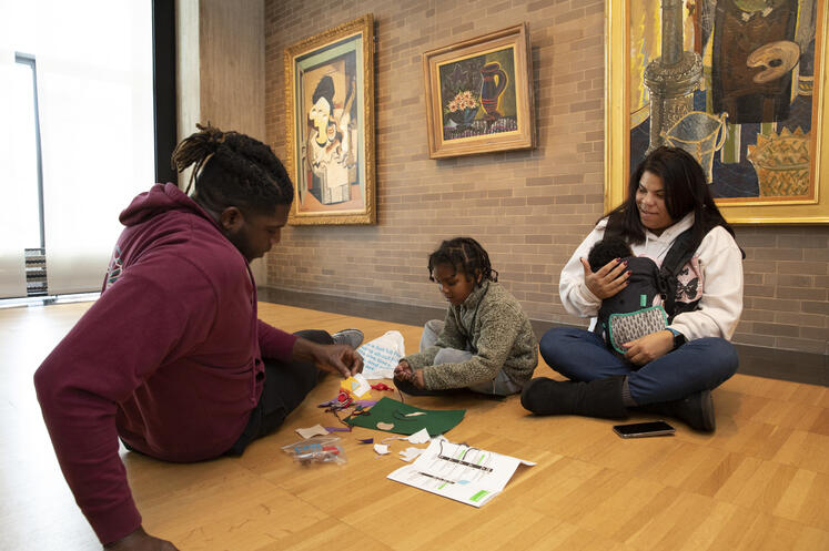 Young boy and his family work on art-making activities during a visit to the Gallery.