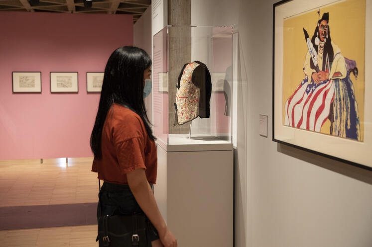 Young woman gazes at lithograph in Place, Nations, Generations, Beings exhibition.