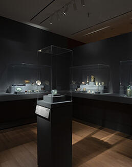 Objects from the collection of ancient glass displayed in glass cases.