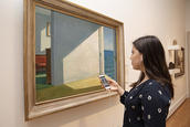 Sara Luzuriaga, BR '21, listens to art historian John Walsh discuss Edward Hopper's Rooms by the Sea (1951) on the Gallery's new app.