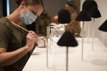 Female art handler paints mounts for objects in the African Art gallery.